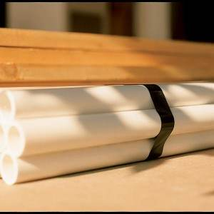 black strapping tape applied around white pvc tubes on wood tabletop