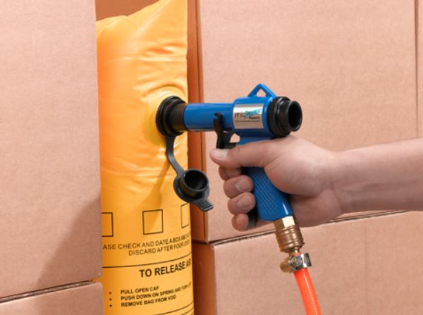handheld inflator filling a yellow vinyl dunnage air bag placed between two corrugated boxes