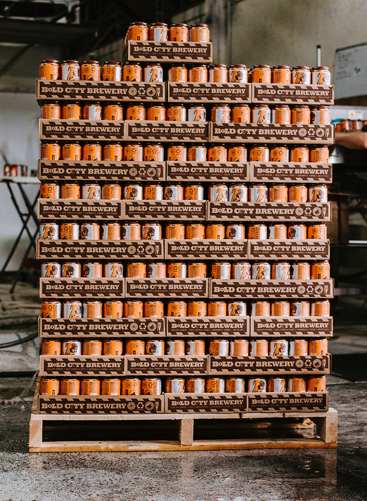 craft beer cans in open boxes stacked onto a pallet