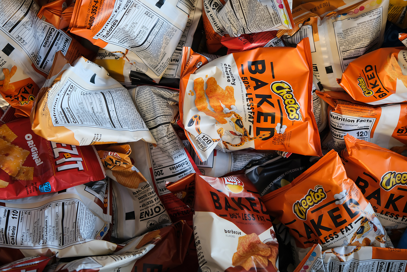 pile of single serve bags of baked cheetos, potato chips, and cheez its