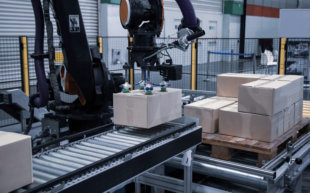 robot picking box from stack and placing onto packaging line conveyor