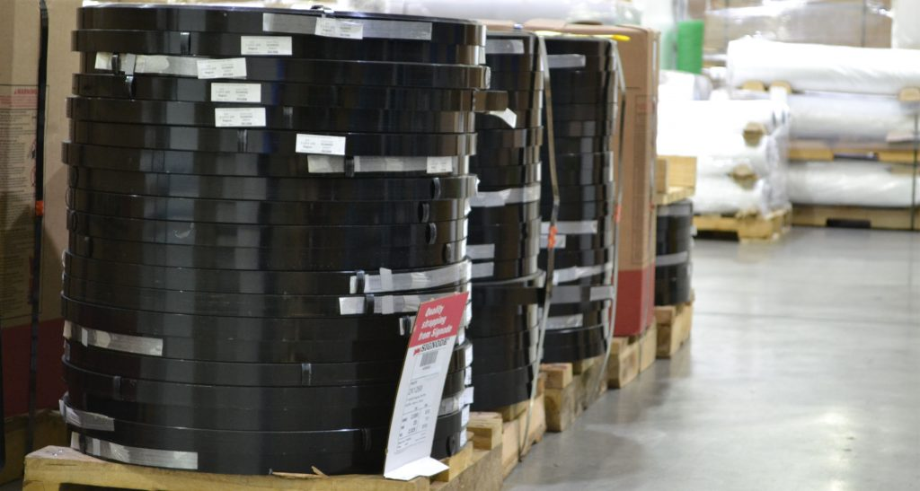 rolls of black strapping in warehouse setting